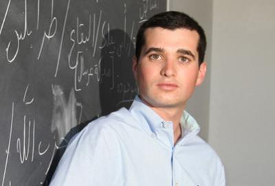 Logan Brog standing in front of chalkboard